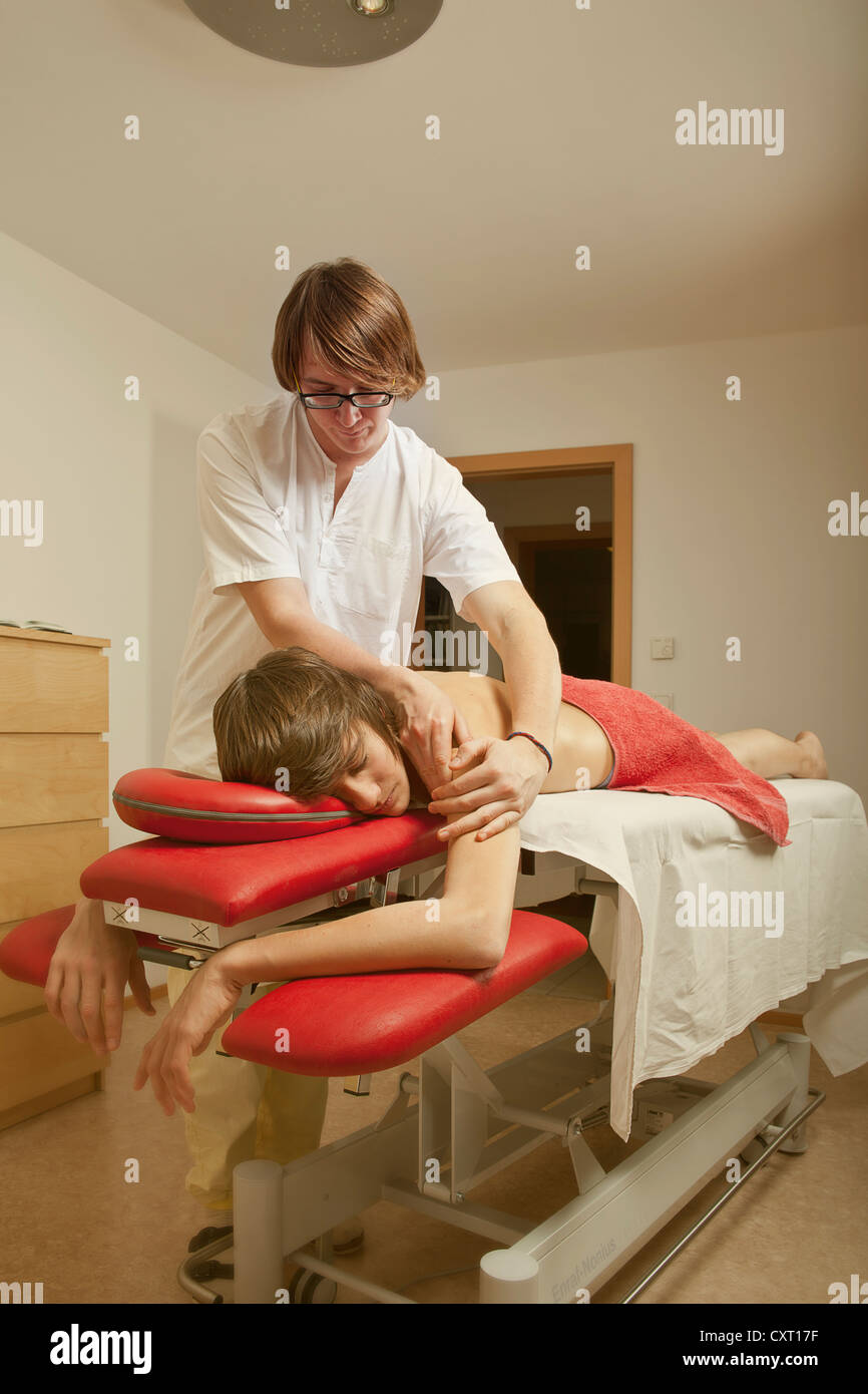 Patient getting a therapeutic massage, massage therapist - Stock Image