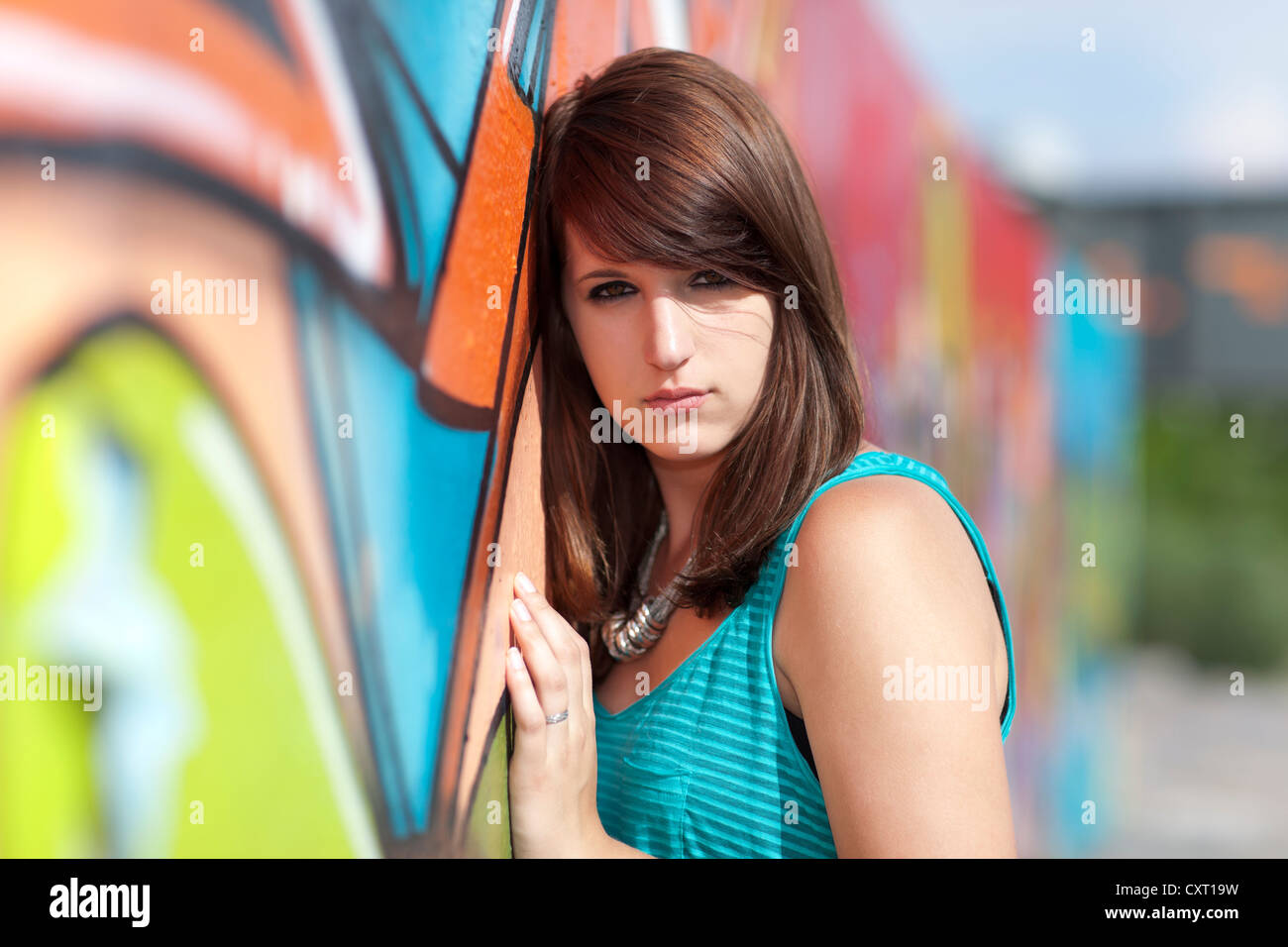 Young woman wearing a turquoise top, black leggings and high heels in front of wall with graffiti, portrait - Stock Image