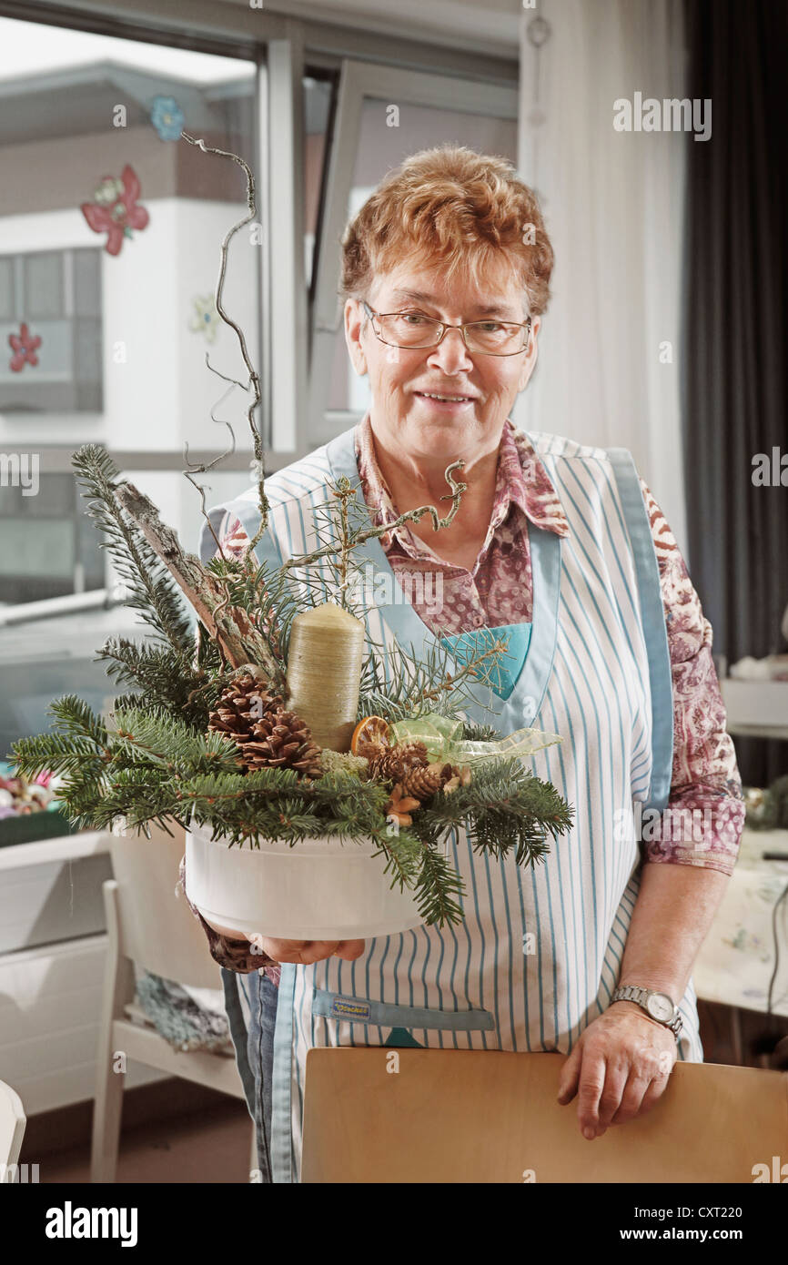 Woman holding a Christmas floral arrangement Stock Photo
