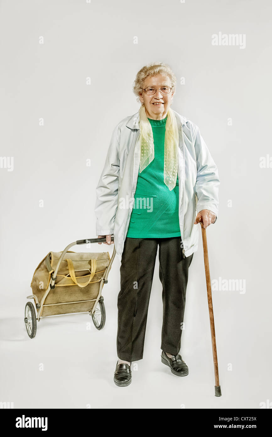 Old woman with a shopping trolley - Stock Image
