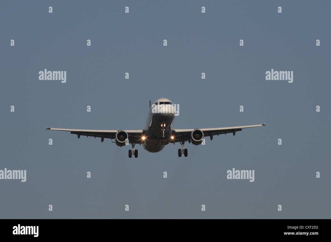 Passenger aircraft during landing approach, from below - Stock Image