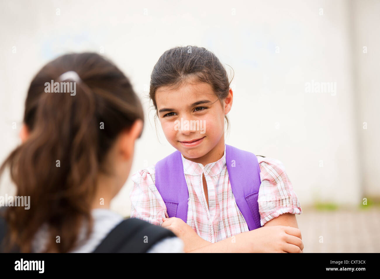 Two girls talking to each other on their way to school - Stock Image