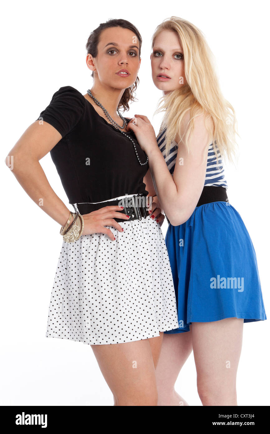 Two young women posing in short skirts - Stock Image
