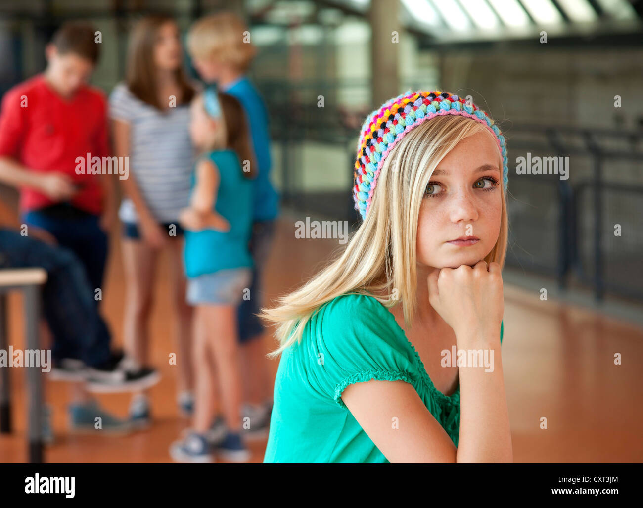 Schoolchildren in a school building, one girl looking sad and isolated from the others - Stock Image