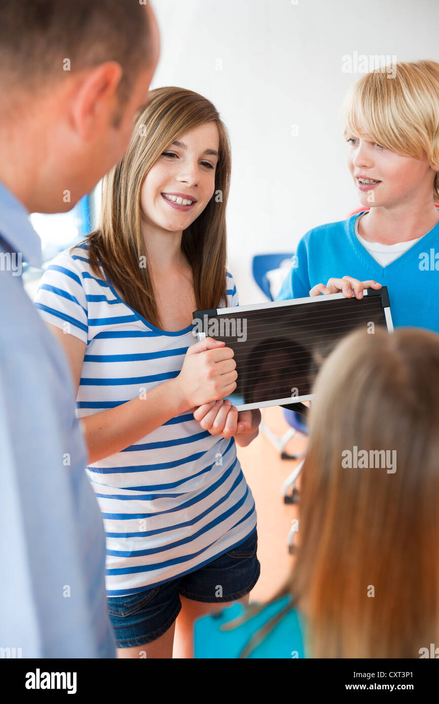 Teacher and schoolchildren in a classroom with a solar panel - Stock Image