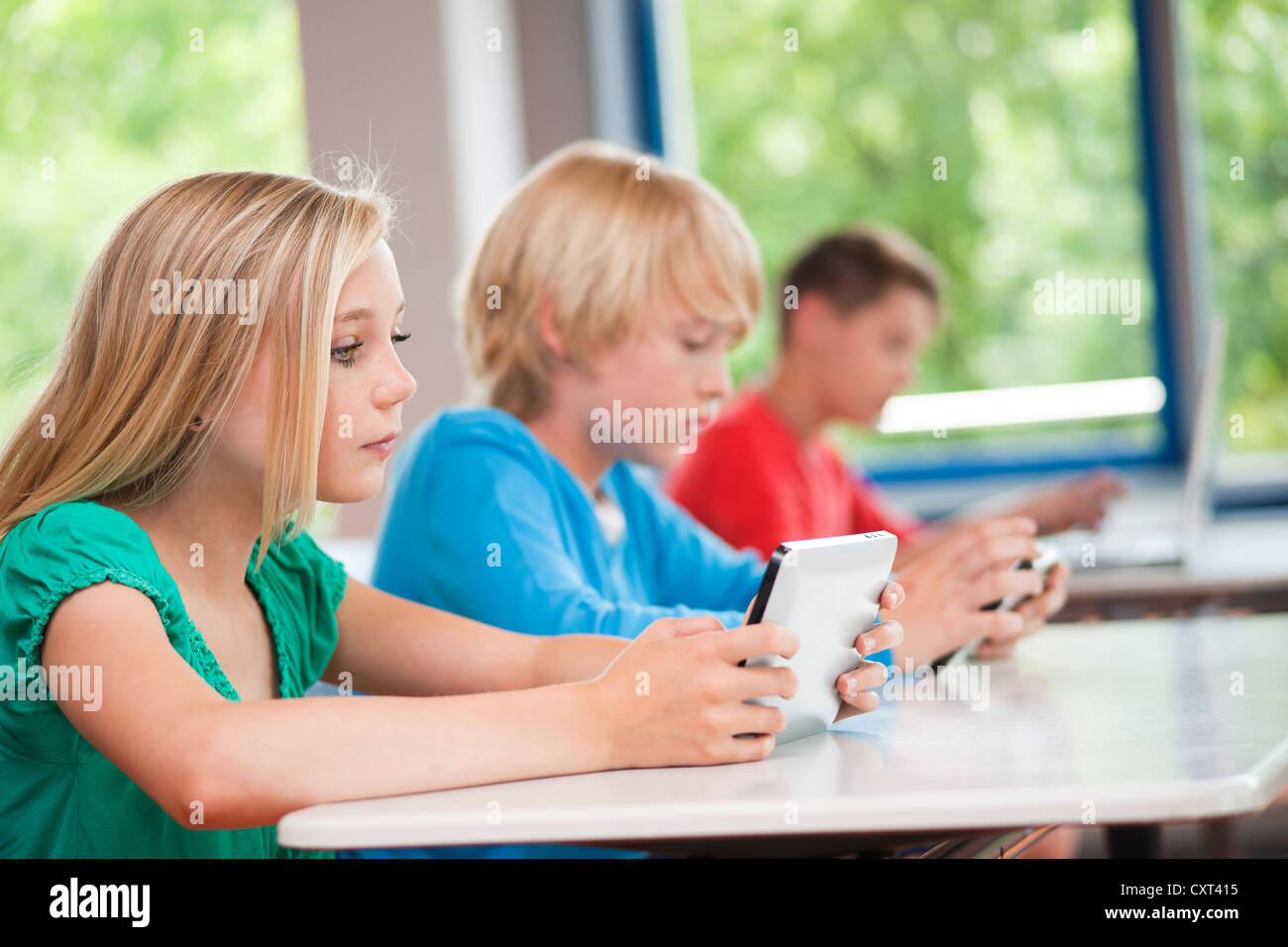 Group of schoolchildren working with computers in a classroom - Stock Image