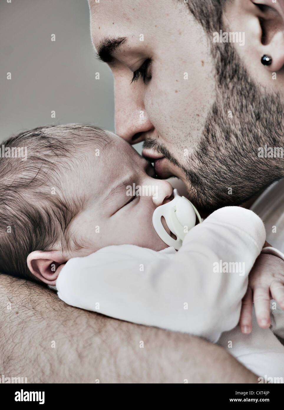 Father lovingly holding his newborn baby in his arms - Stock Image