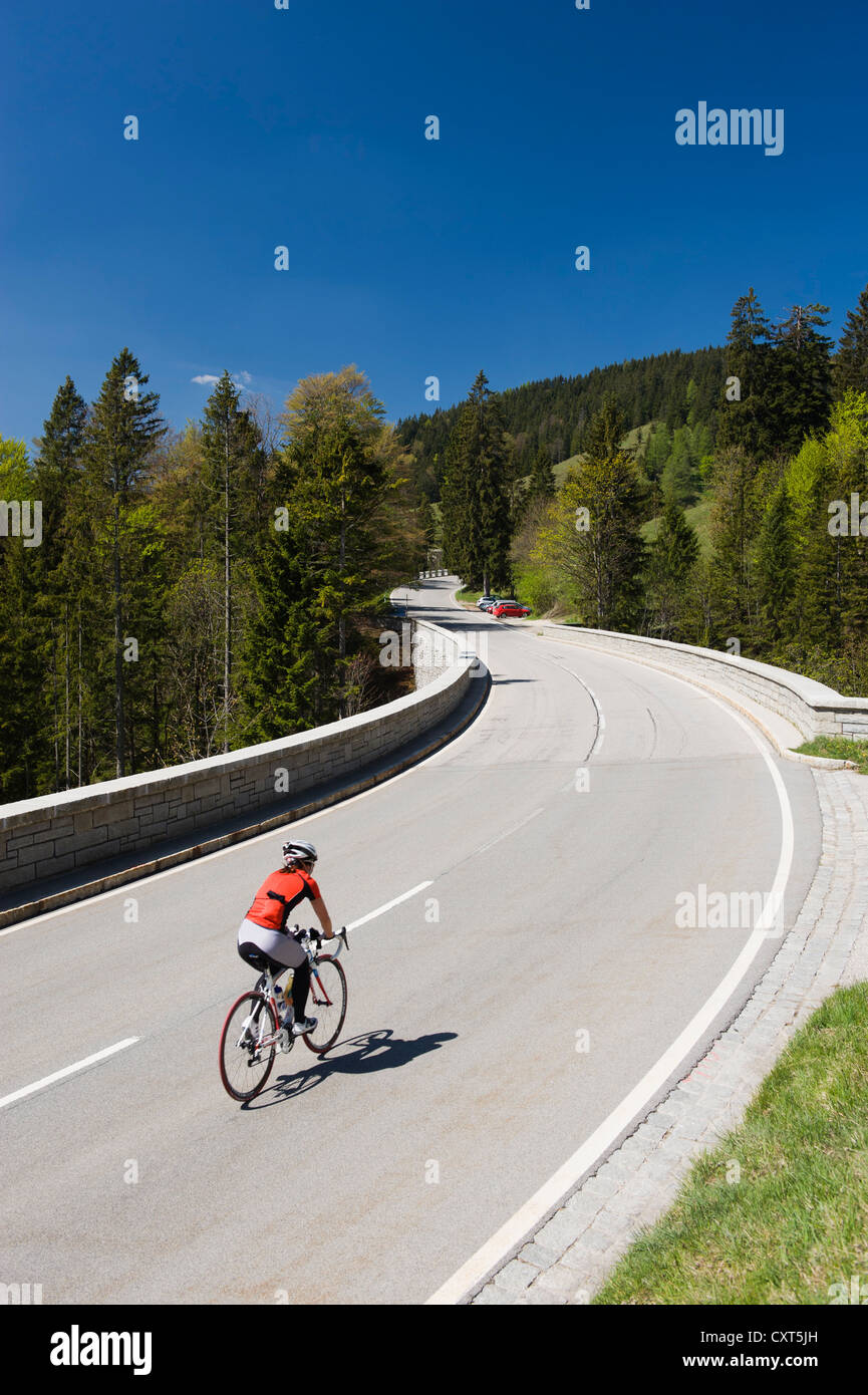 A cyclist is travelling up the mountain road to Tatzelwurm lake, Bavarian Alps, Upper Bavaria, Bavaria - Stock Image
