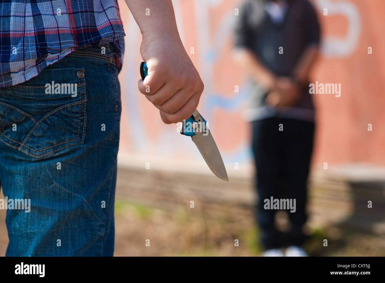 Boy is threatened by a youth with a knife - Stock Image