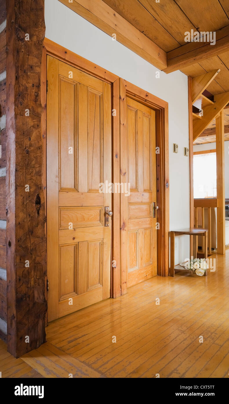 Hallway closet and bathroom doors inside a reconstructed cottage-style residential log home, 1982, Quebec, Canada. - Stock Image
