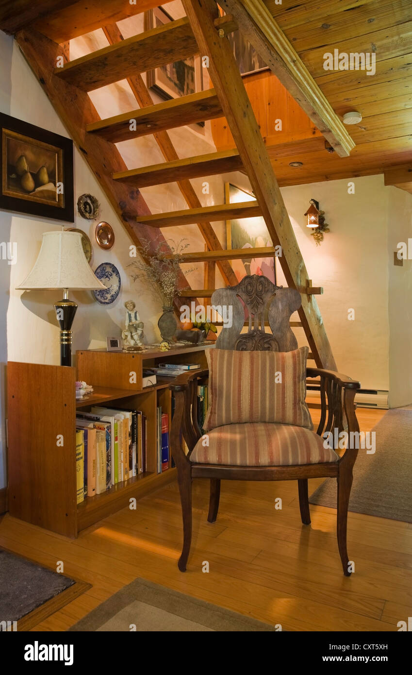 Chair and bookcase beneath the stairs in an old Canadiana cottage-style residential fieldstone home, circa 1740, - Stock Image