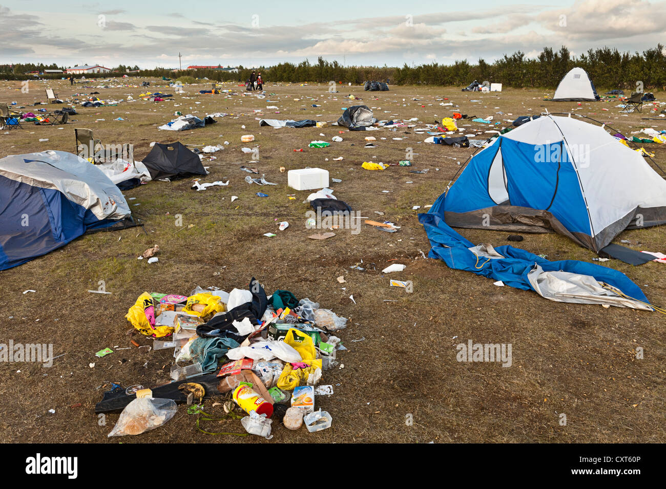 meadow full of garbage, waste, destroyed tents and broken camping