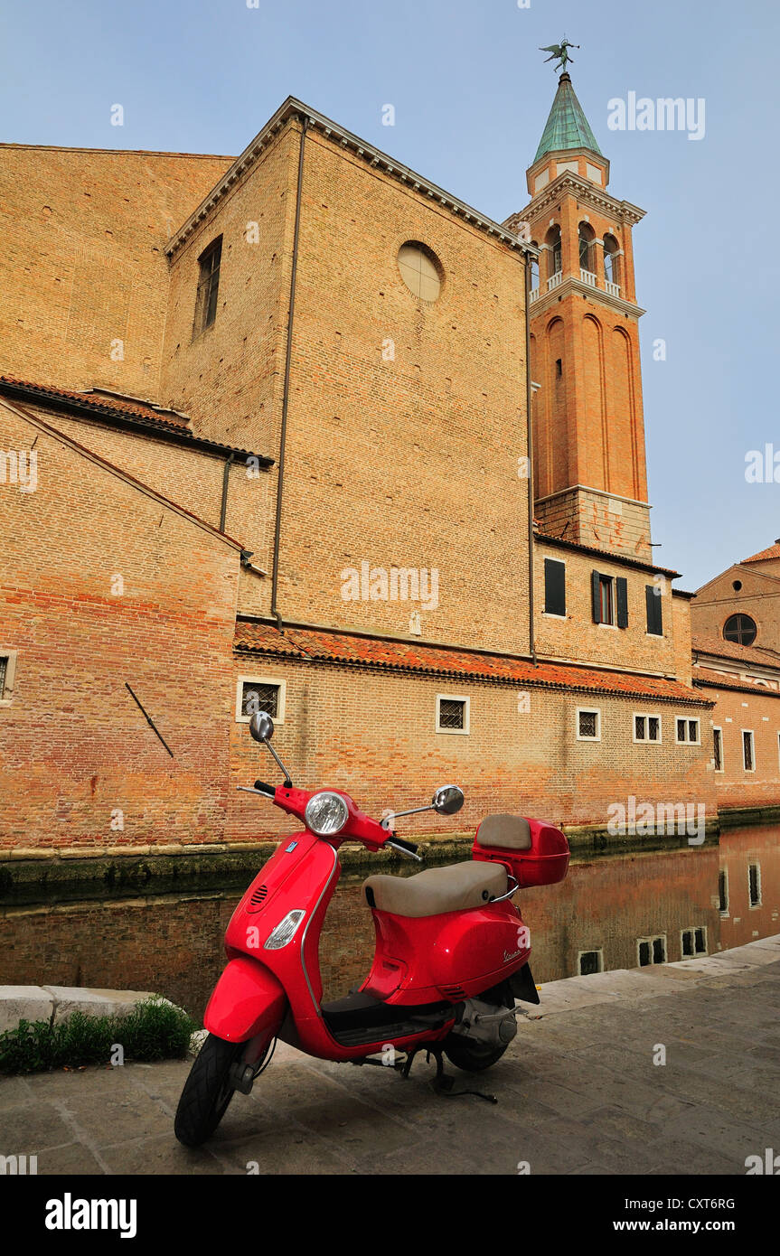 Red Vespa motor scooter parked in front of the cathedral, Chioggia, Veneto, Italy, Europe - Stock Image