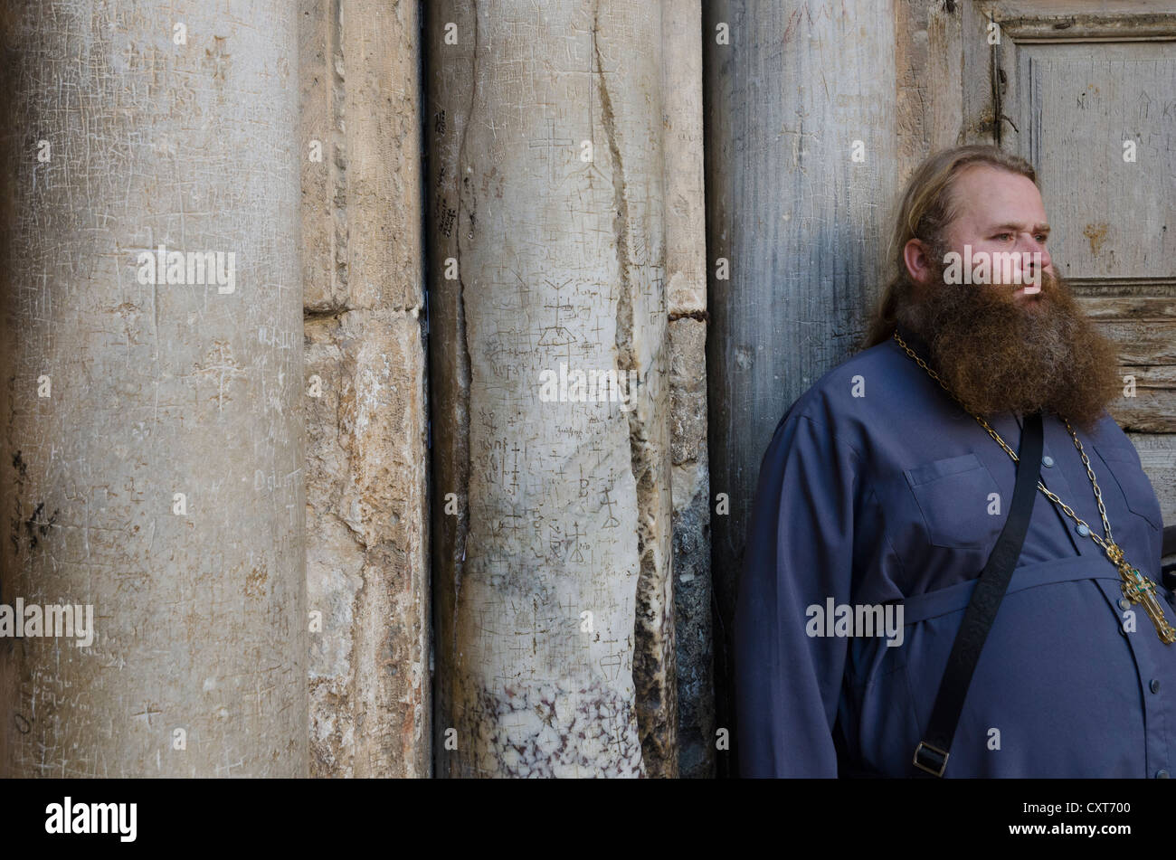 Russian orthodox priest standing next to columns at the entrance to the Holy Sepulcher. Jerusalem Old City. Israel. - Stock Image