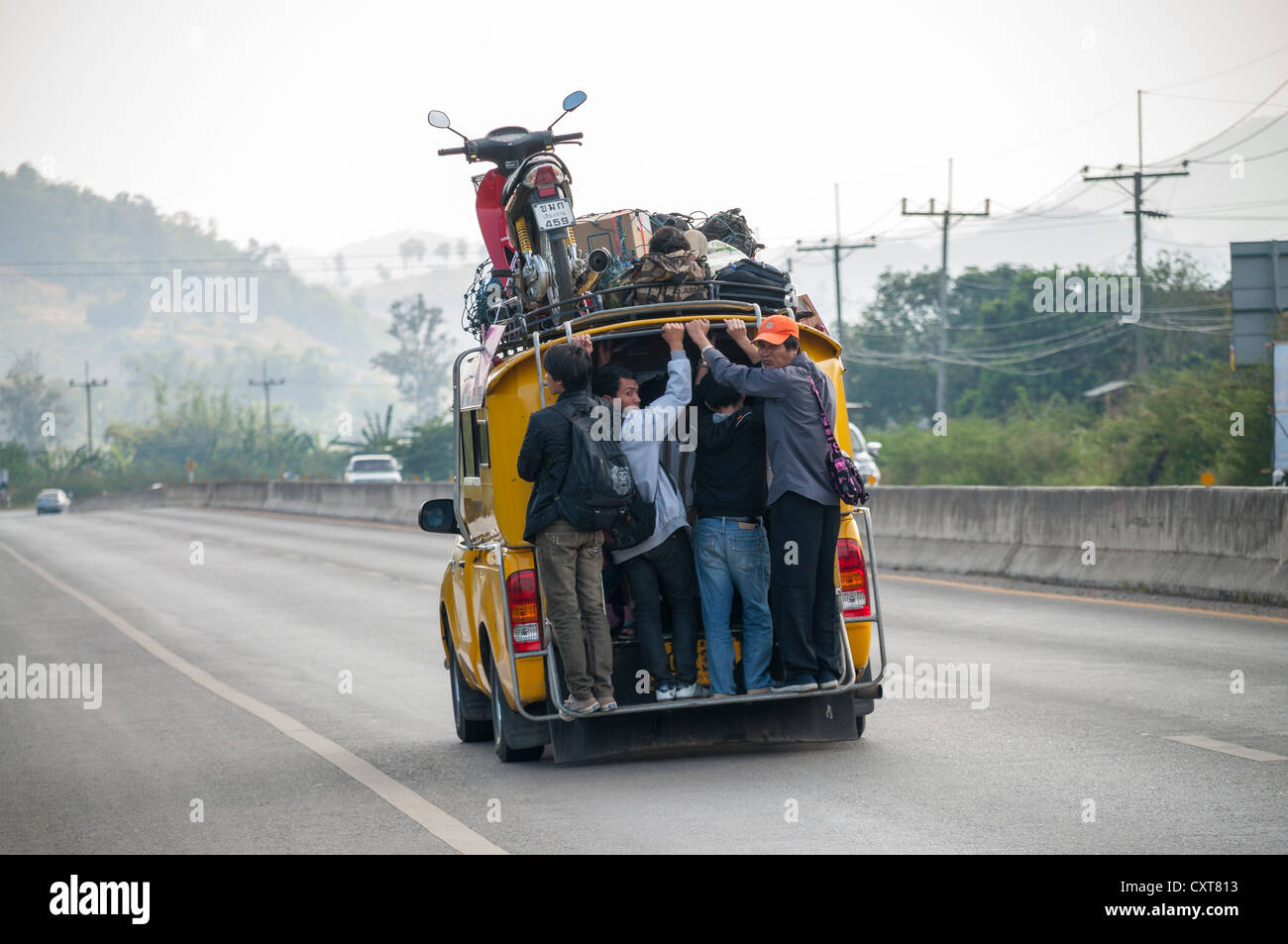 Overcrowded share taxi or Songthaew on a road, a motor bike loaded on the roof, northern Thailand, Thailand, Asia - Stock Image