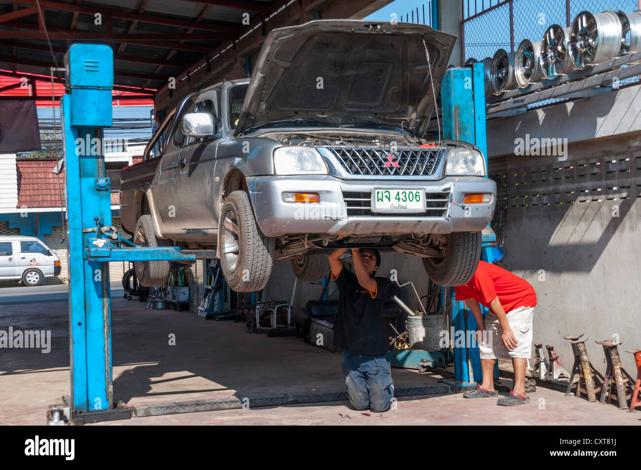 Suv or pick up on a lift or a hoist in a garage car for Garage reparation auto