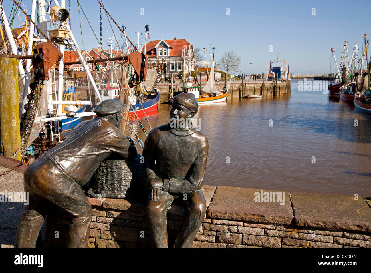 Old fisherman and young fisherman, sculpture by Hans-Christian Petersen in the old fishing port of Neuharlingersiel, Stock Photo