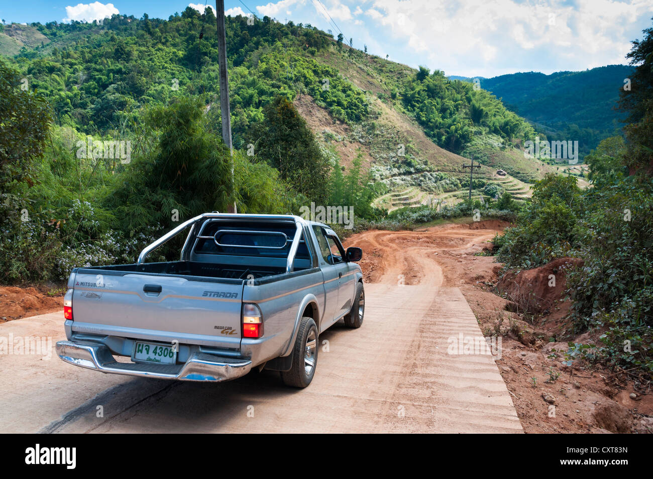 SUV or pick-up truck at the end of a paved road, dirt road, Northern Thailand, Thailand, Asia - Stock Image