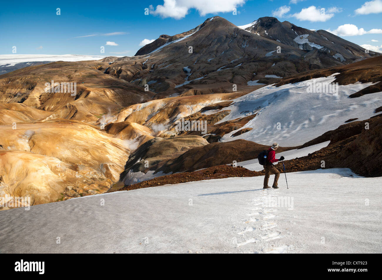 Hiker crossing the snowfield on a trail, snow-capped Rhyolite Mountains, Hveradallir high temperature area, Kerlingarfjoell - Stock Image