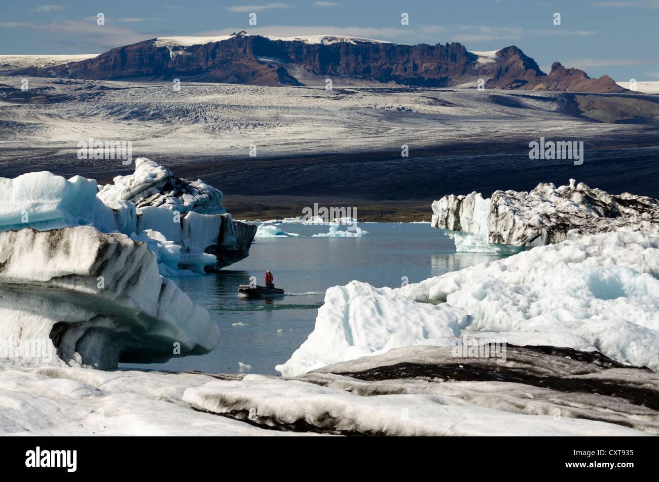 Zodiac raft or inflatable boat, partly black ash-coloured icebergs, glacier lagoon of Joekulsárlón, Vatnajoekull - Stock Image