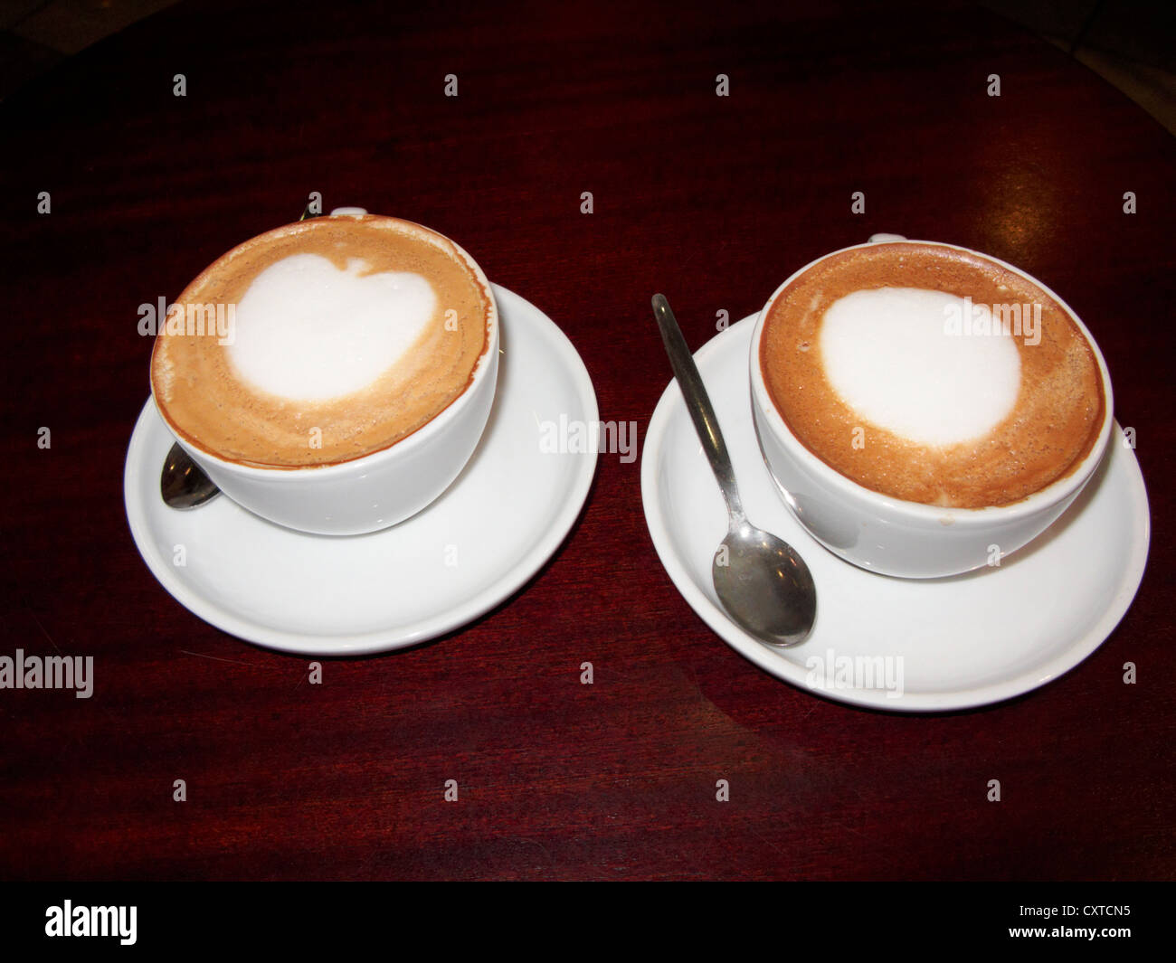 two cups of mocha coffee on a table in a coffee shop in the uk united kingdom - Stock Image