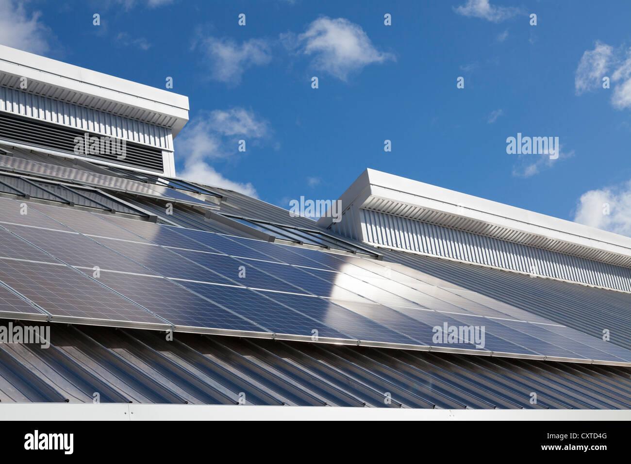 Solar panels on school roof against blue sky in sunshine - Stock Image