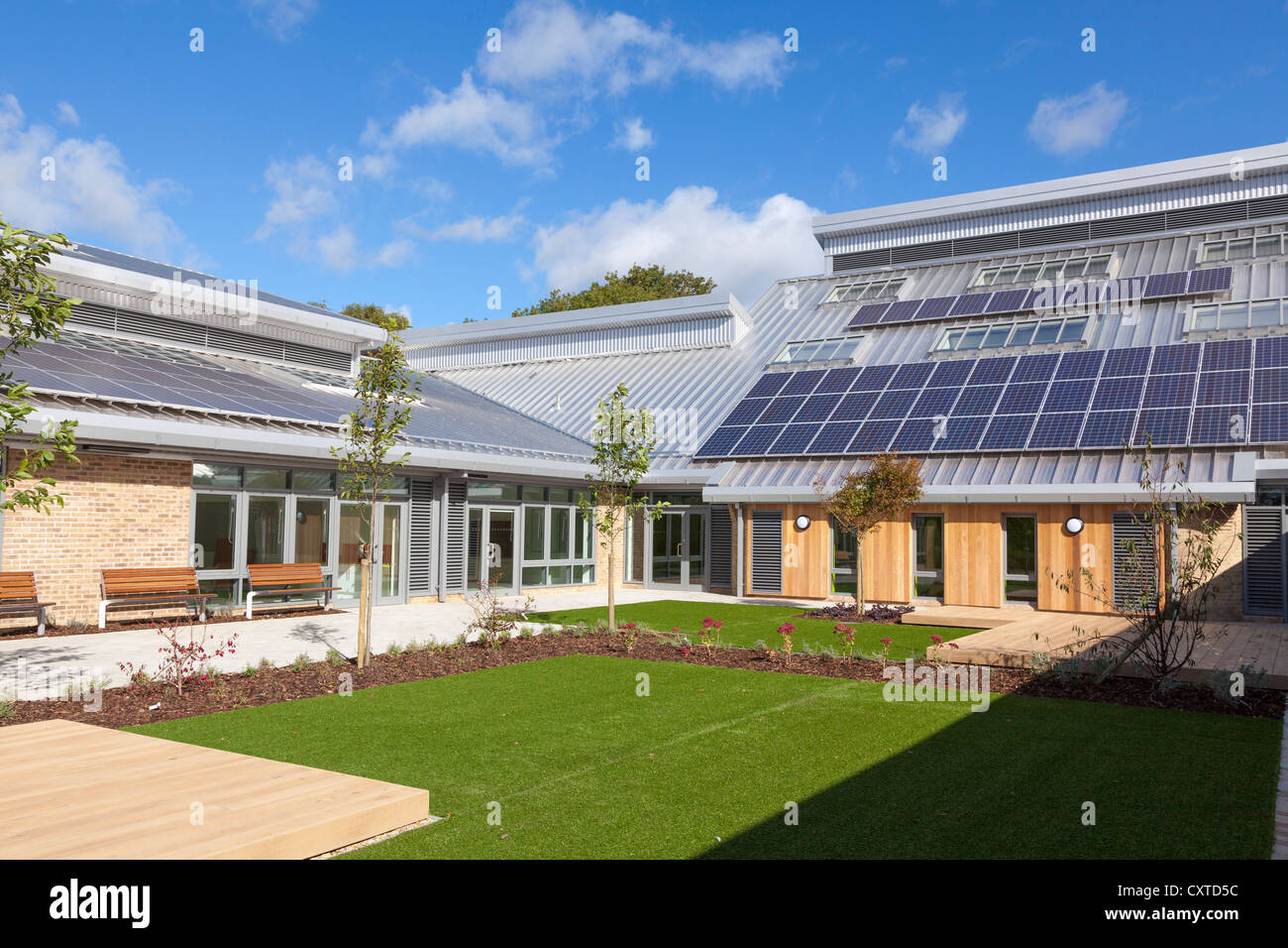 Courtyard of new build primary school with solar panels in sunshine. - Stock Image