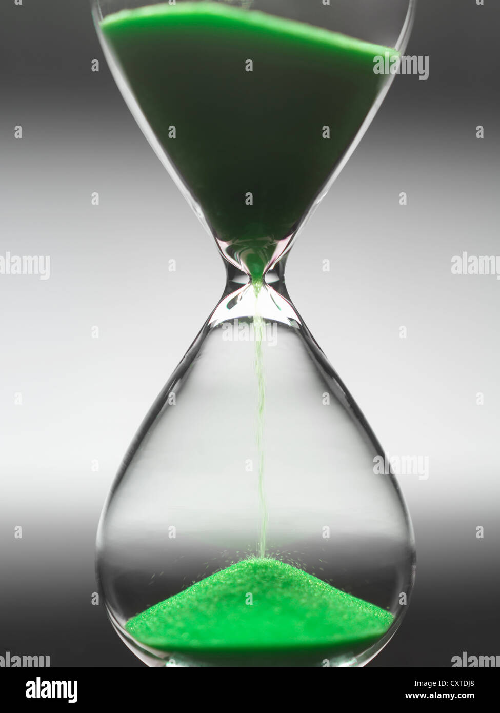 Green sand pouring through hourglass - Stock Image