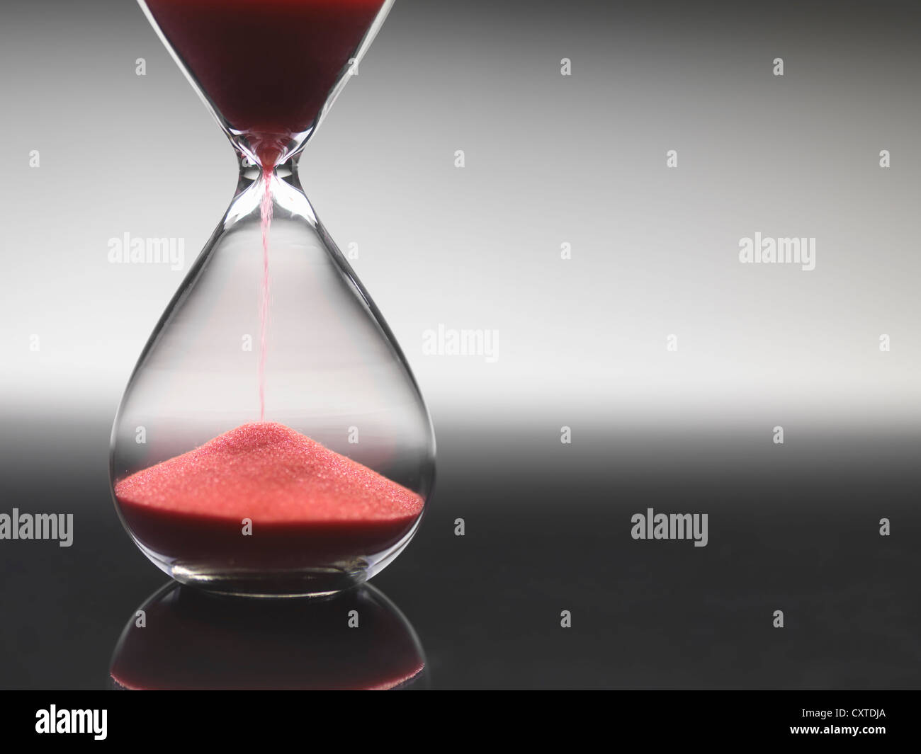 Pink sand pouring through hourglass - Stock Image