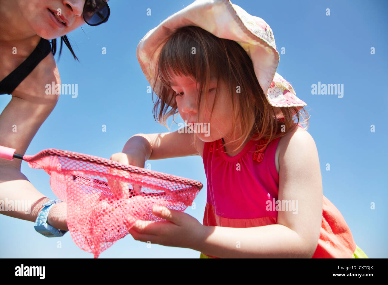 Mother and daughter fishing with net - Stock Image