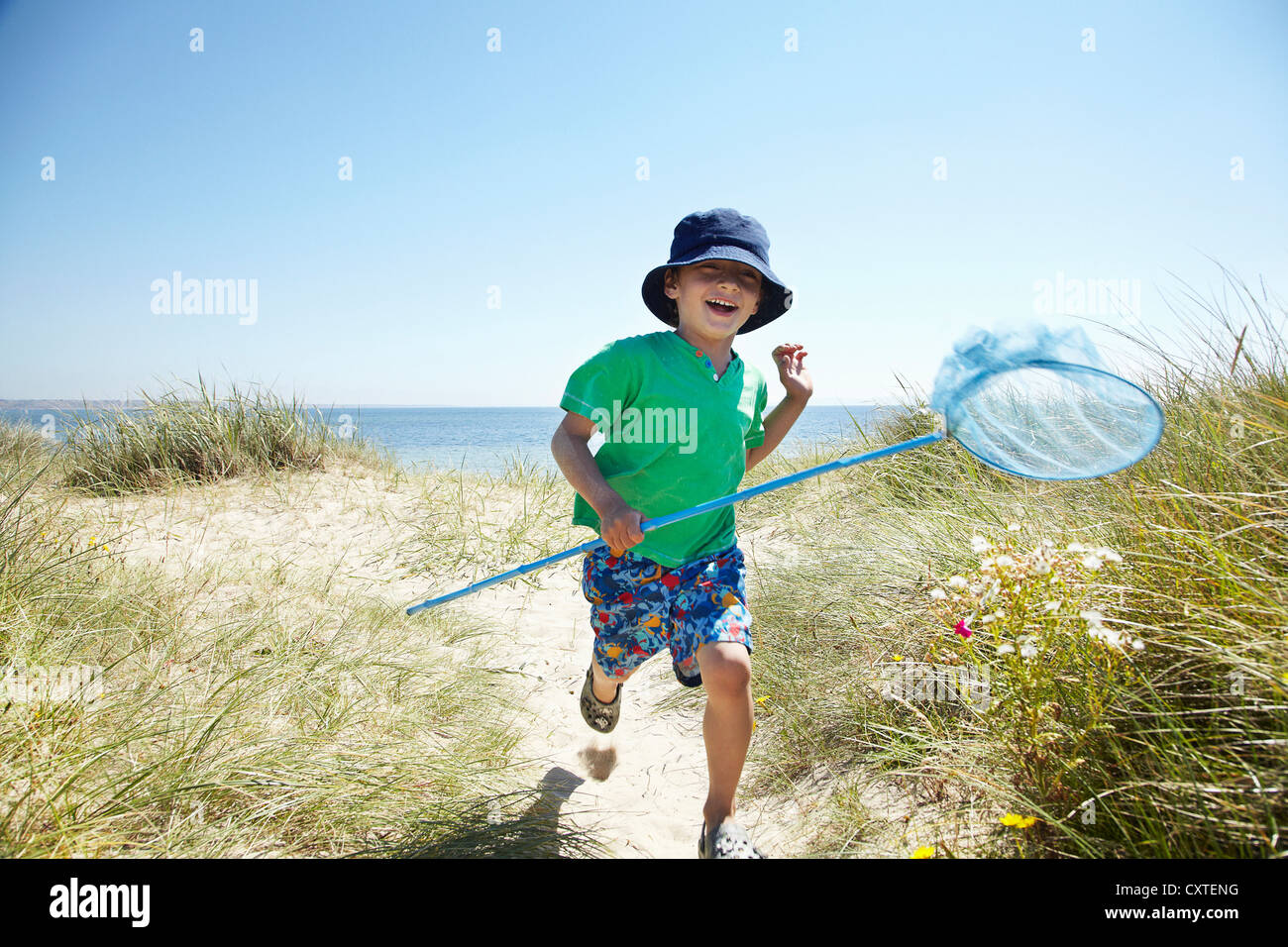 Boy carrying fishing net on beach - Stock Image