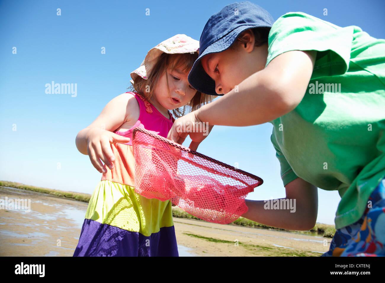 Children examining fishing nets - Stock Image