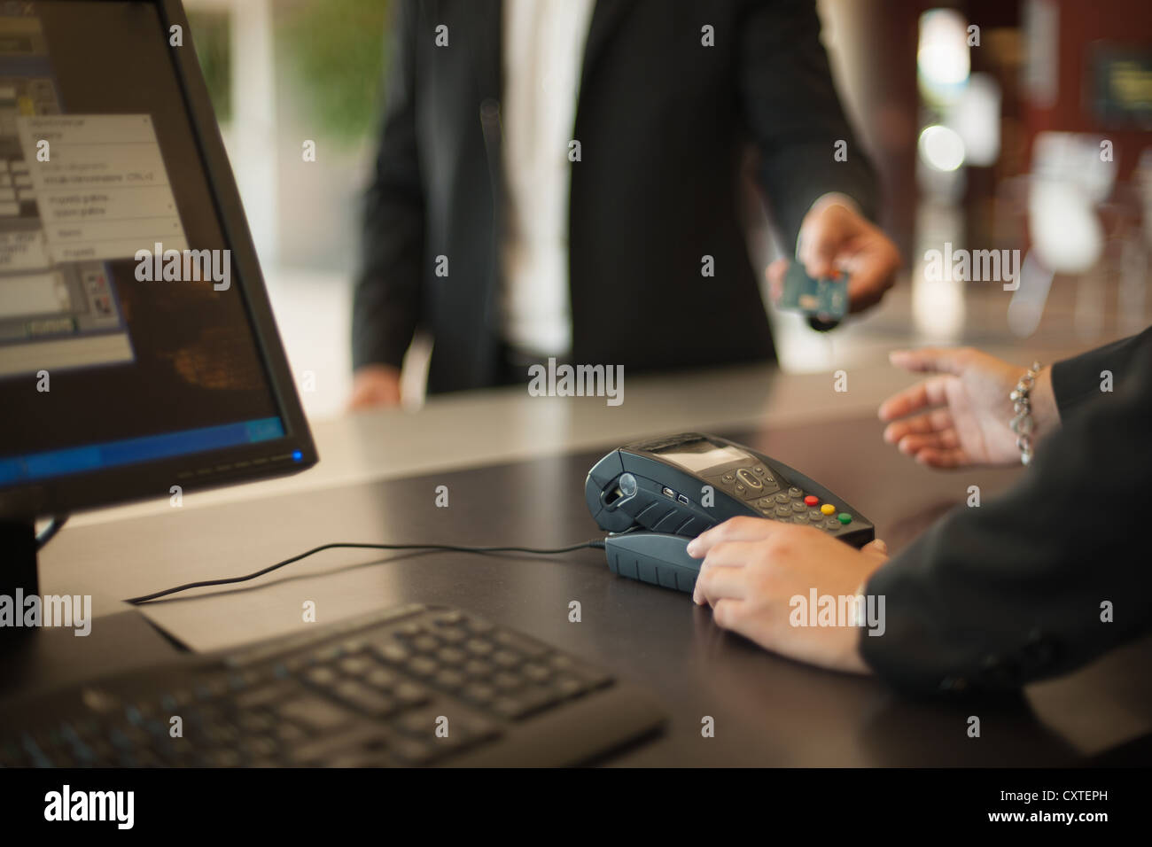 Businessman checking into hotel - Stock Image