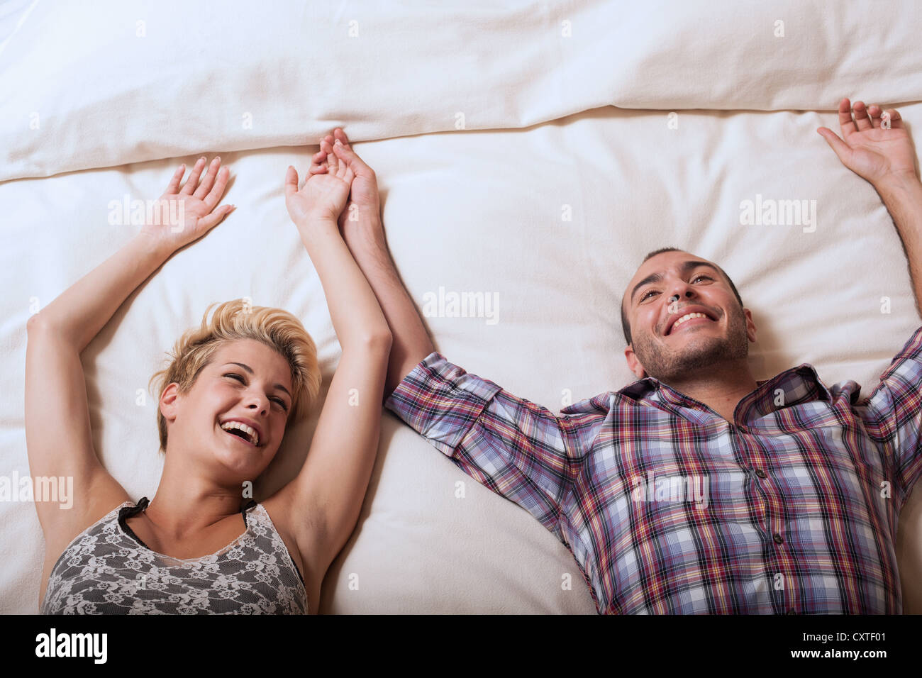 Couple relaxing on hotel room bed - Stock Image