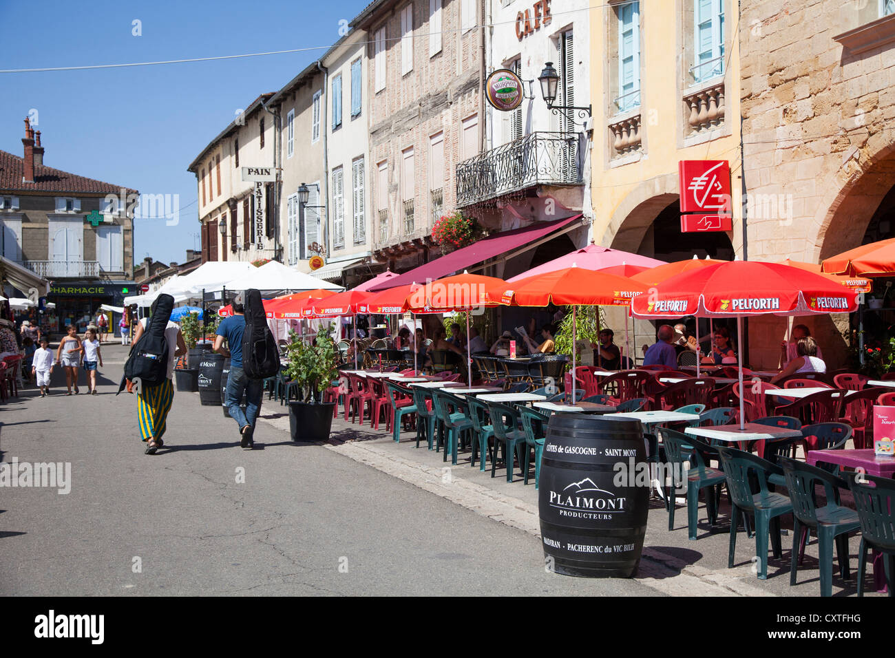 Marciac during the Jazz festival with musicians walking down the main road and cafes, Marciac, Gers, Midi Pyrenees, - Stock Image