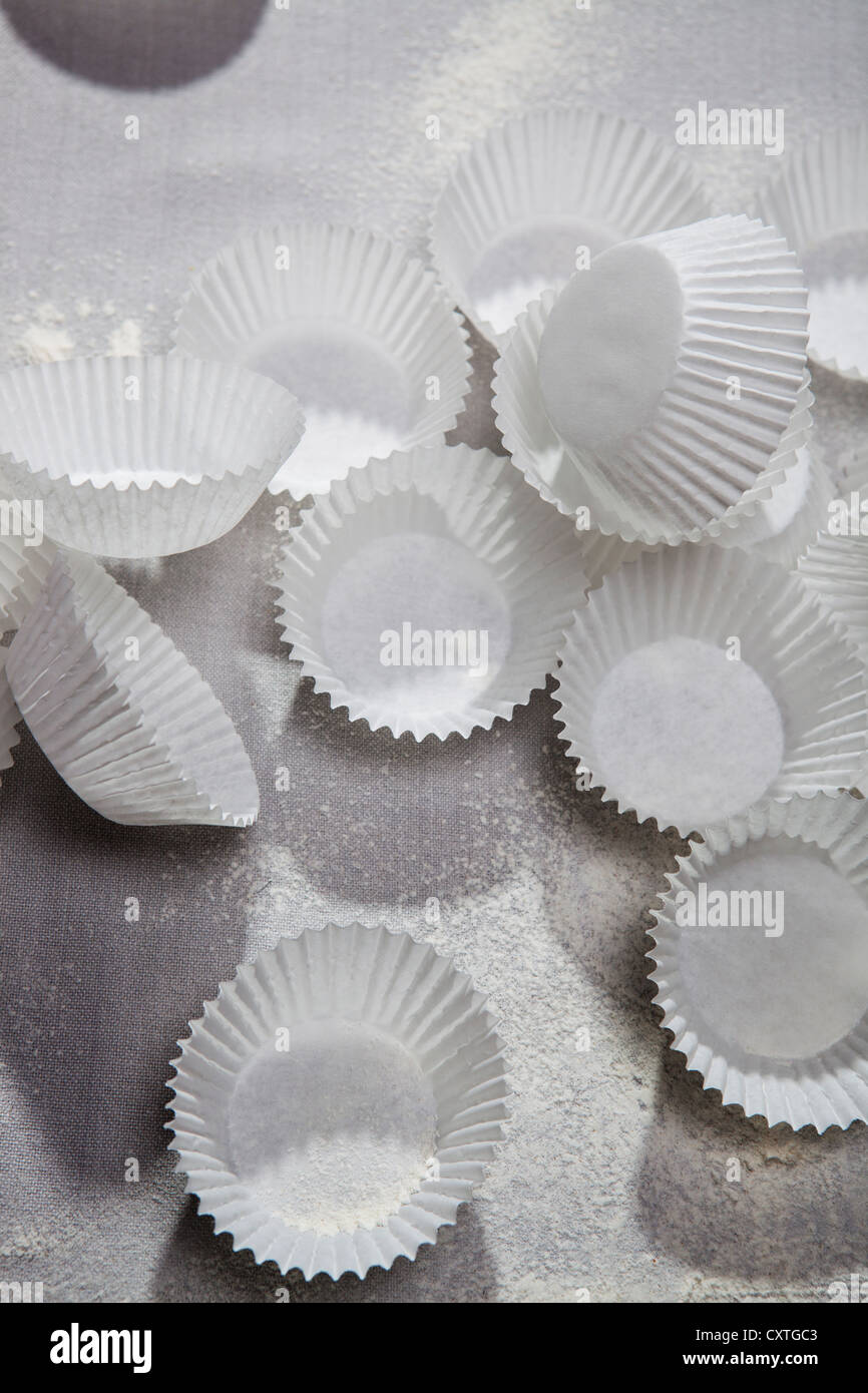 Cupcake wrappers and flour on table - Stock Image