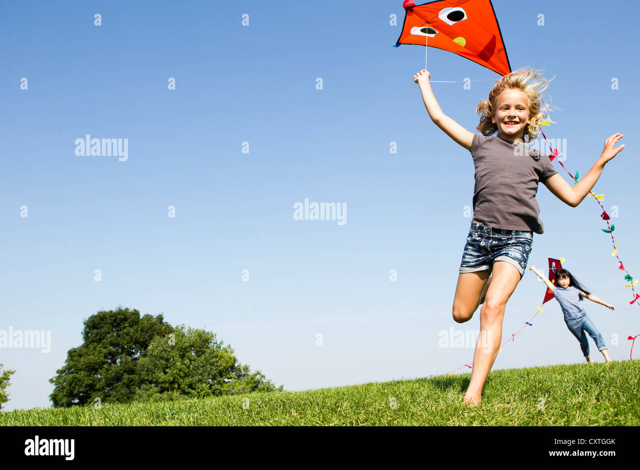 Girls playing with kites outdoors - Stock Image