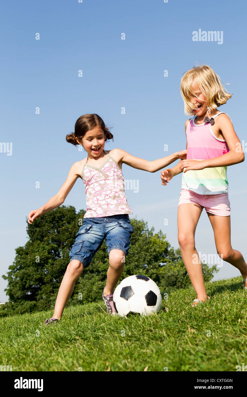 Girls playing soccer in field - Stock Image