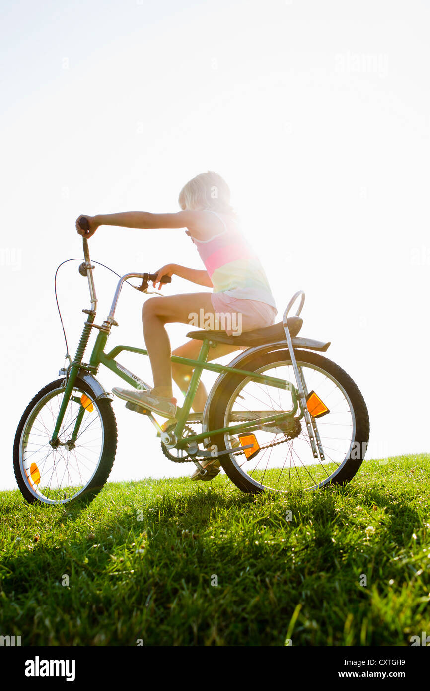 Girl riding bicycle in grass - Stock Image