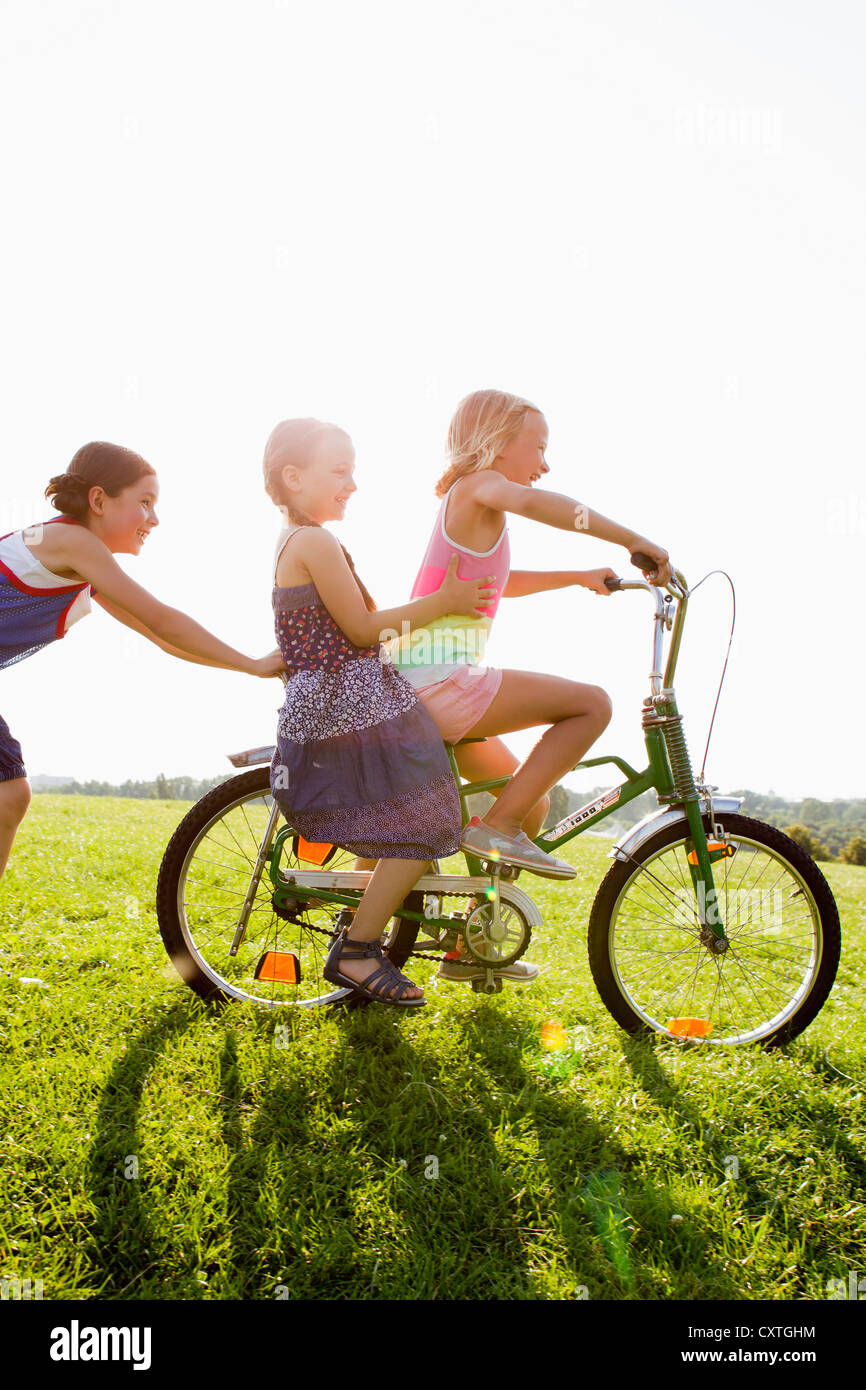 Girls playing with bicycle in grass - Stock Image