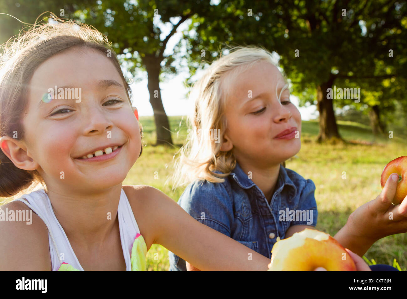 Laughing girls eating apples outdoors - Stock Image