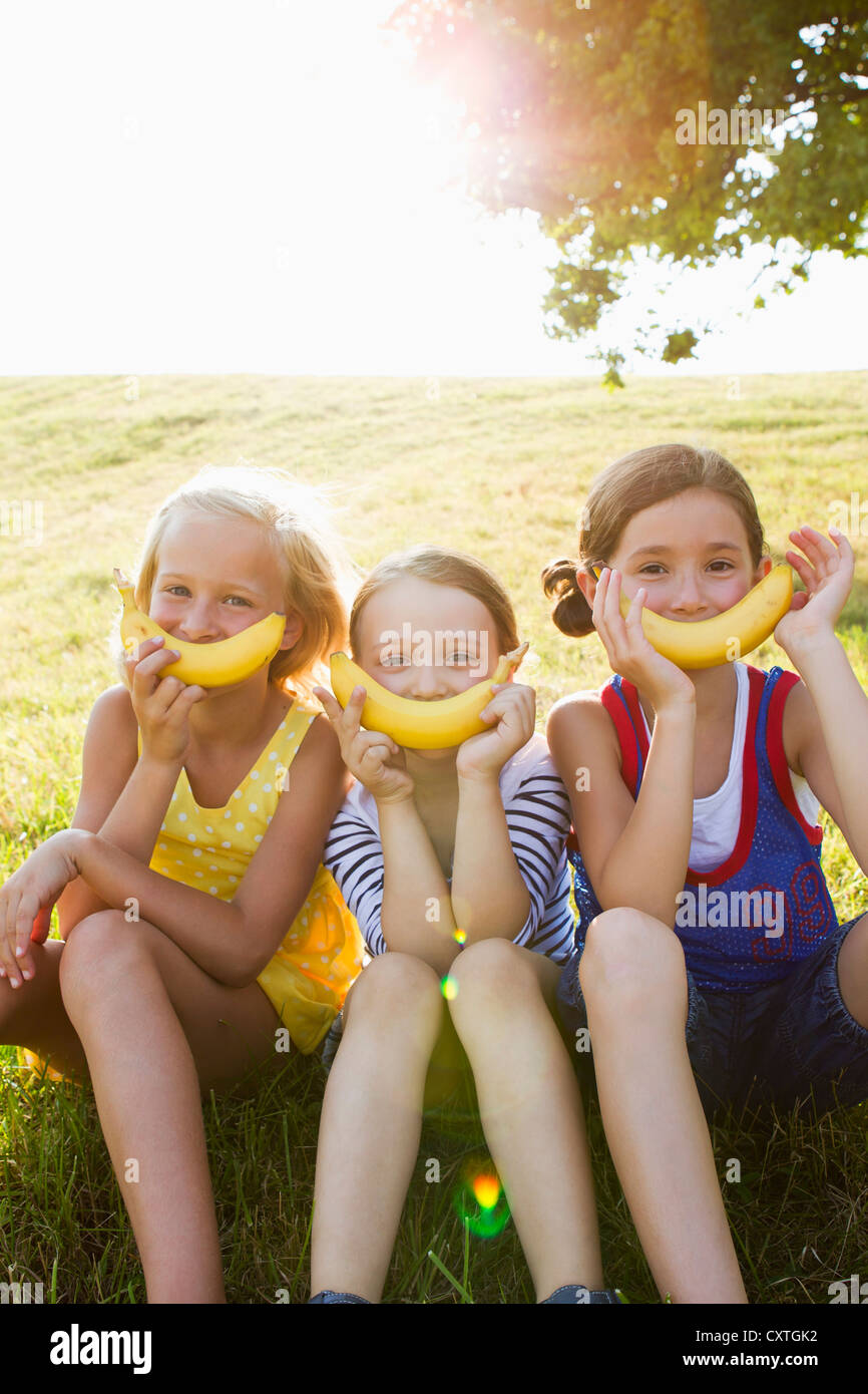 Girls holding bananas over mouths - Stock Image