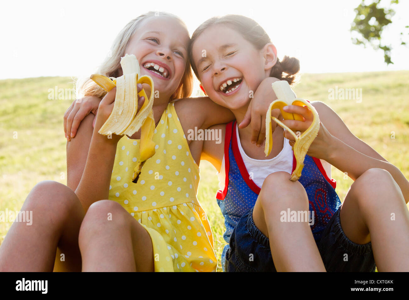 Laughing girls eating bananas outdoors - Stock Image
