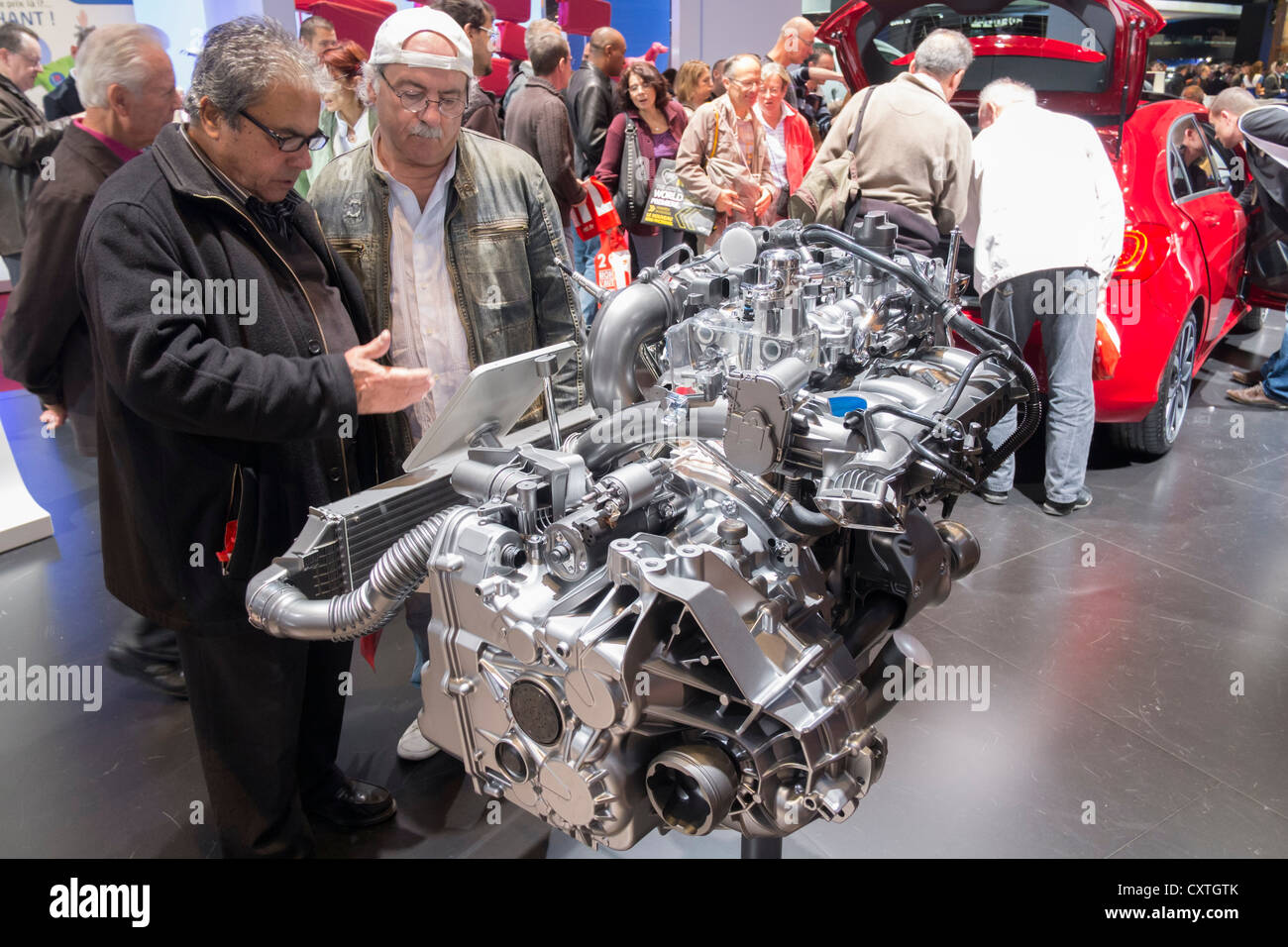 Visitors look at new petrol engine by Mercedes benz at Paris Motor Show 2012 - Stock Image