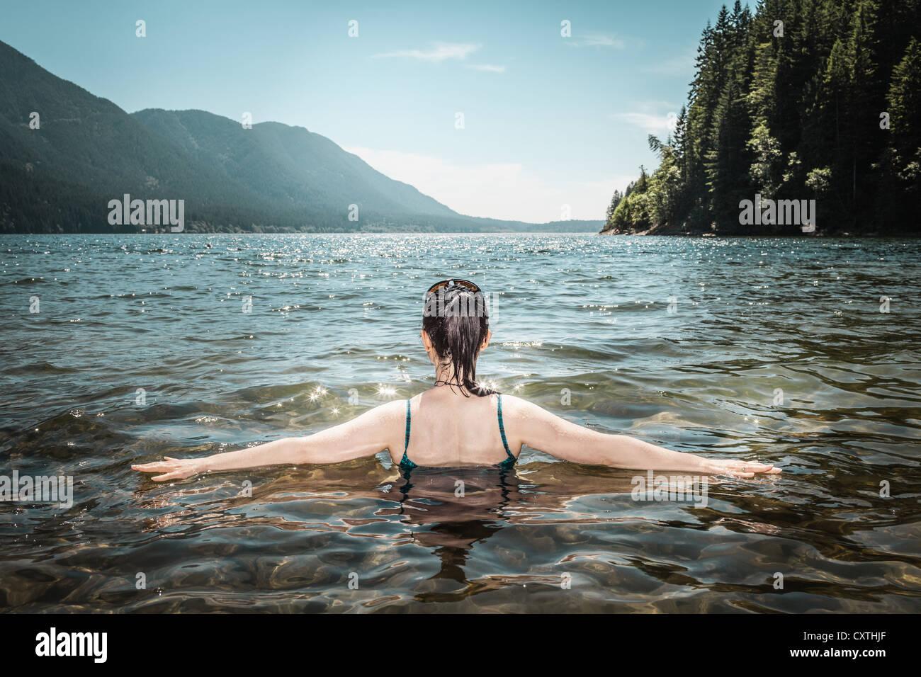Woman walking in still lake - Stock Image