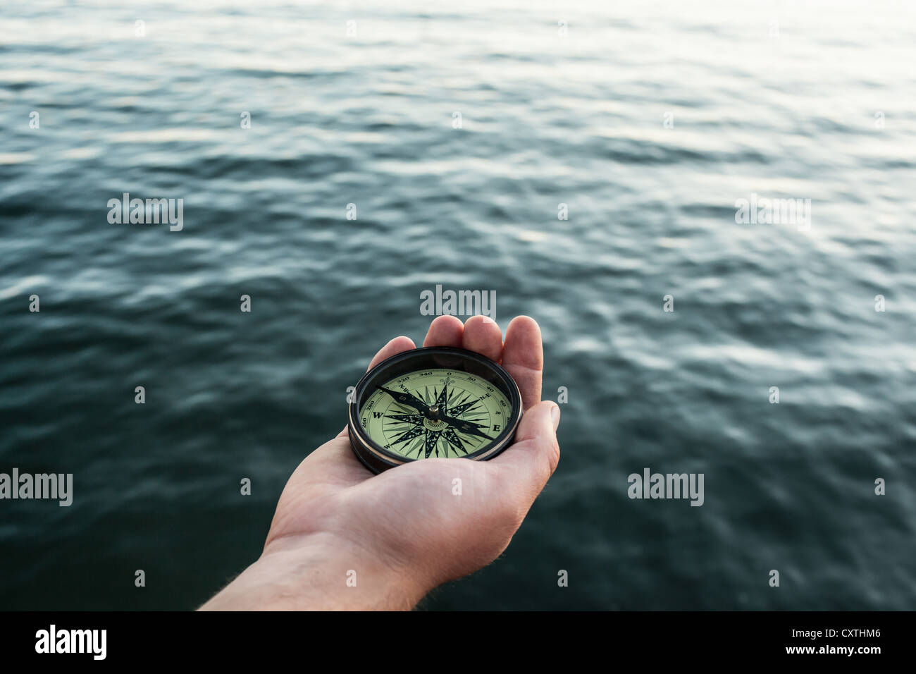 Close up of hand holding compass - Stock Image