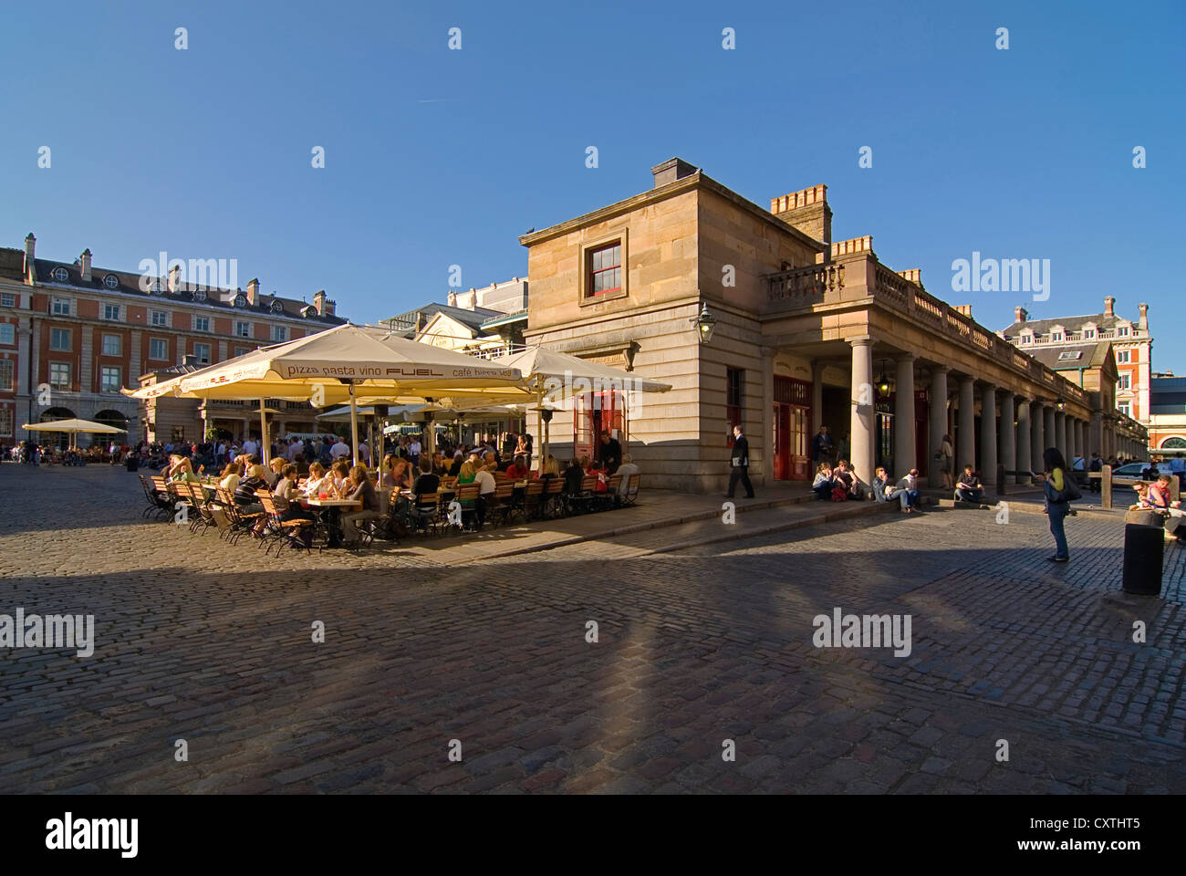Horizontal wide angle of people enjoying a leisurely drink in the evening sun at one of the street cafes in Covent Stock Photo