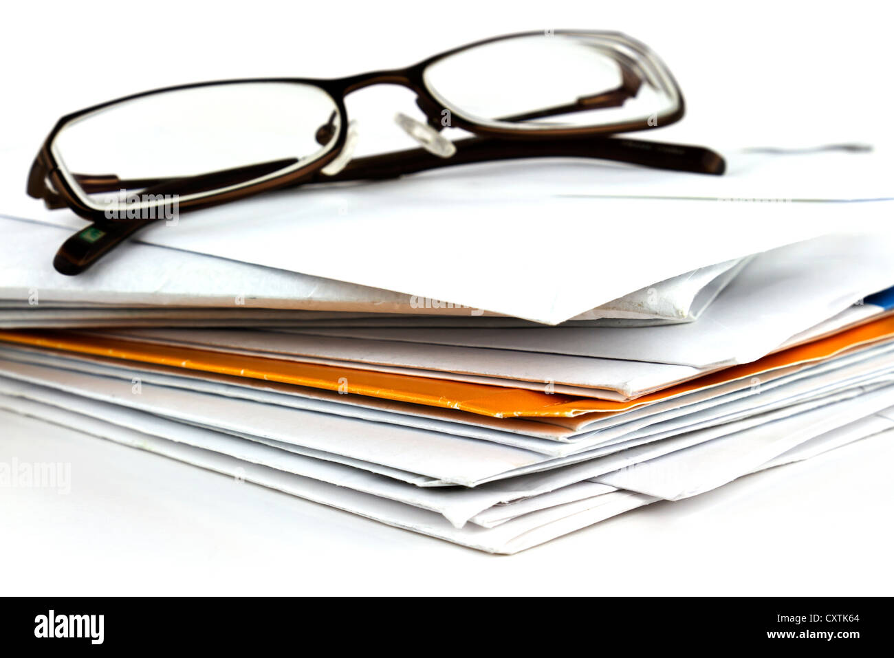 Stack of postal mail with pair of eyeglasses on white background. - Stock Image