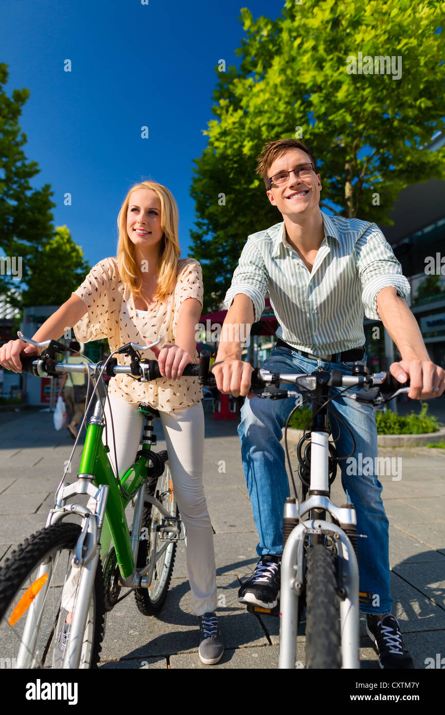 Couple - man and woman - riding their bikes or bicycles in their free time and having fun on a sunny summer day - Stock Image