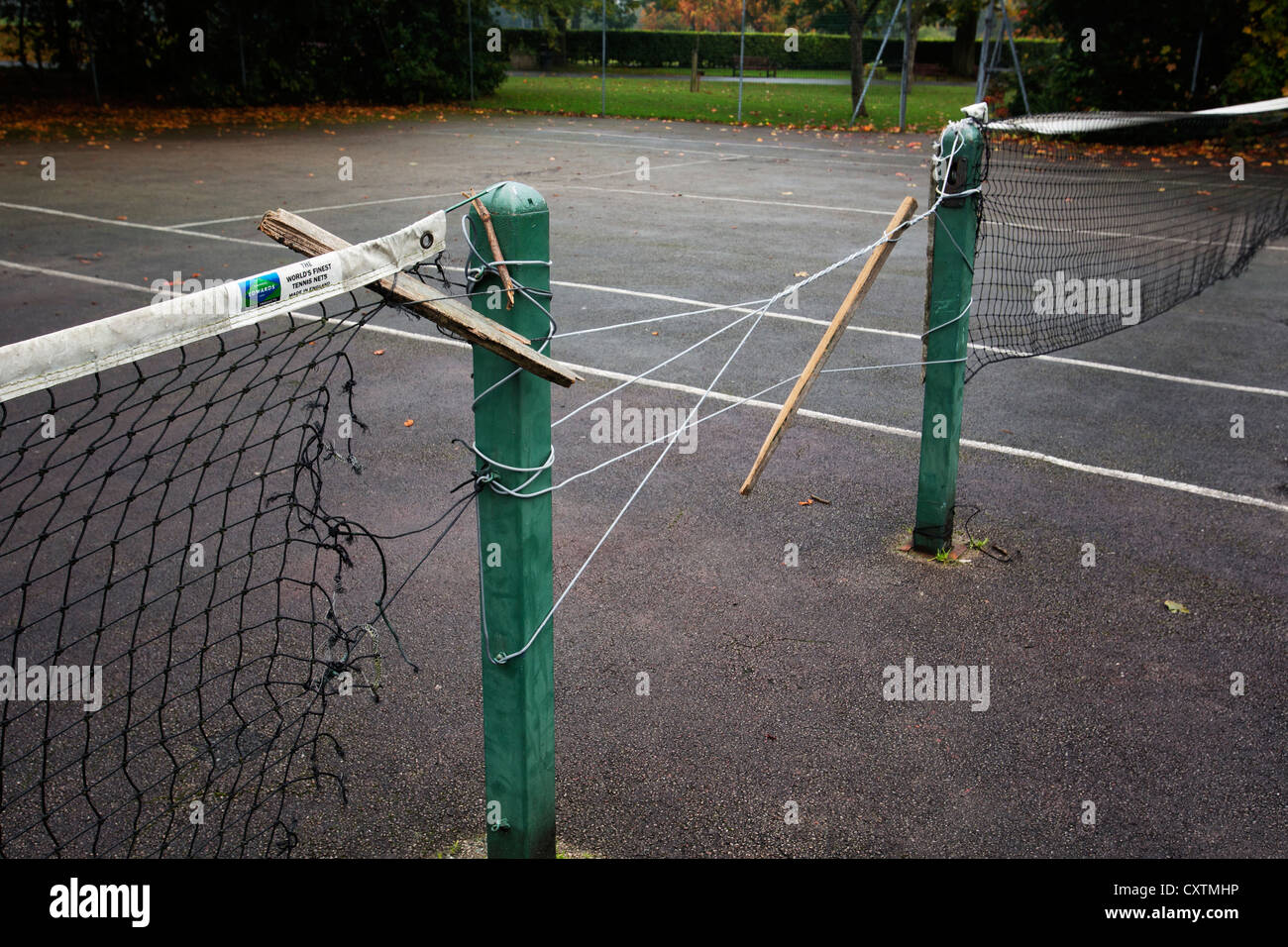 Tennis nets in disrepair on municipal park courts in the UK. - Stock Image